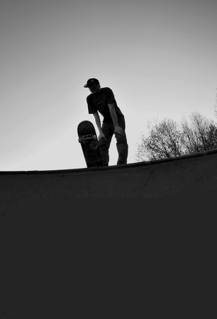 individualism: silhouette of a skateboarder standing on top of a massive skateboard ramp