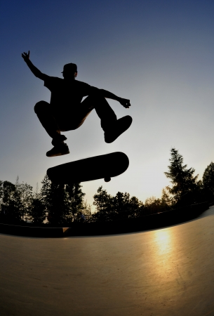 skateboarding: perfect silhouette of a skateboarder doing a flip trick at the skate park