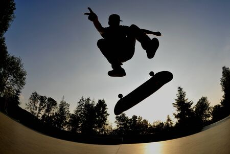 perfect silhouette of a skateboarder doing a flip trick at the skate park   photo