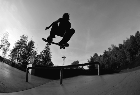 skaters: perfect silhouette of a skateboarder doing a flip trick at the skate park