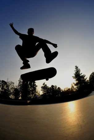 halfpipe: perfect silhouette of a skateboarder doing a flip trick at the skate park