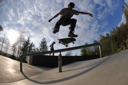 ni�o en patines: skateboarder que se divierten en el parque local del pat�n