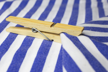 clothepeg: Wooden clothes peg on a blue and white textile