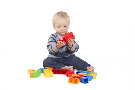 blocks: Blond young boy is playing with coloured cubes Stock Photo