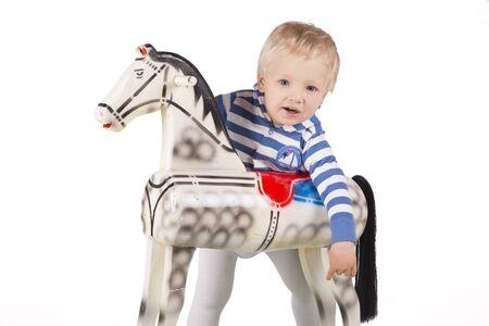 rocking: Blond boy riding wooden rocking horse