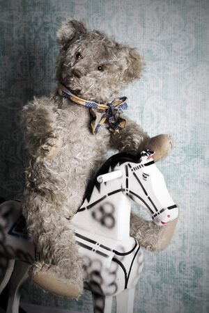 cute teddy bear: Unsightly vintage Teddy bear riding an old wooden rocking horse Stock Photo
