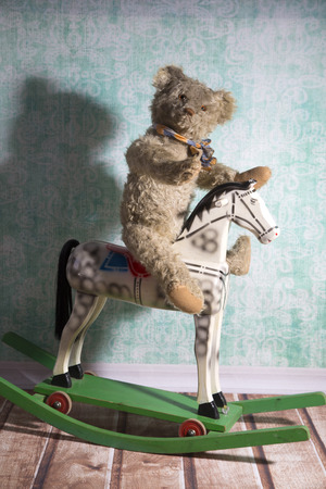 unsightly: Unsightly vintage Teddy bear riding an old wooden rocking horse Stock Photo