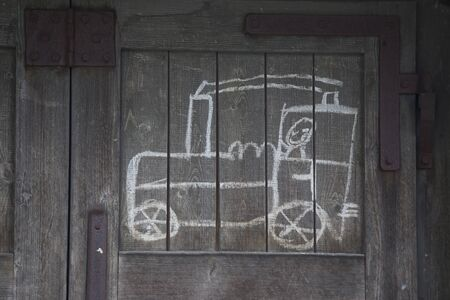 scamp: childs drawing of a train on an old wooden wall Stock Photo