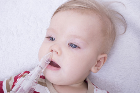 aspirator: Mother using nasal aspiration for infant, mucus suction