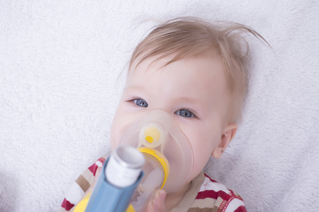 oxygen: Infant using an asthma inhalator Stock Photo
