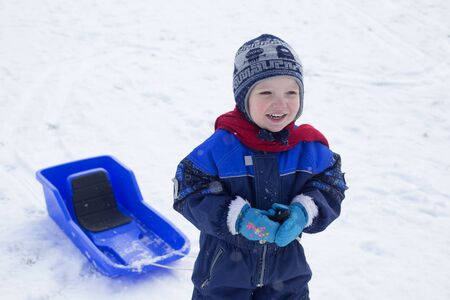Young boy and his plastic sled