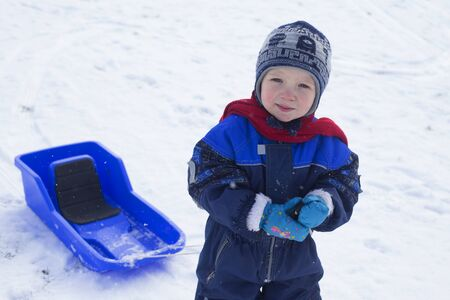 merrymaking: Young boy and his plastic sled