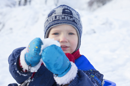 merrymaking: Young boy playing with a snowball
