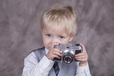 Jonge blonde jongen die retro camera in fotostudio houdt