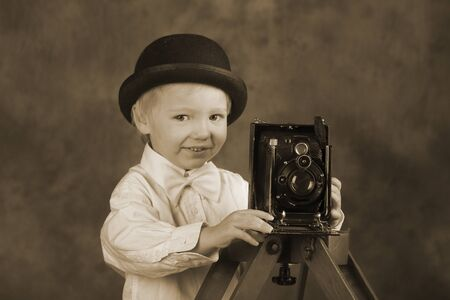 Young blond boy holding retro camera with bellows in photo studio, photographer, vintage sepia tone