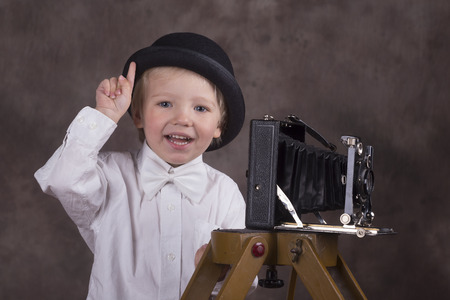 bellows: Young blond boy holding retro camera with bellows in photo studio, photographer Stock Photo