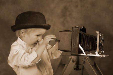 bellows: Young blond boy holding retro camera with bellows in photo studio, photographer, vintage sepia tone