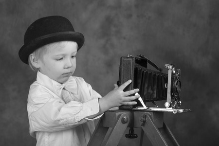 bellows: Young blond boy holding retro camera with bellows in photo studio, photographer, black and white photo