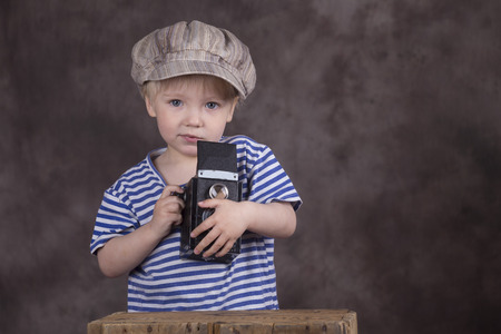 reflex camera: Young blond boy holding retro twin-lens reflex camera in photo studio, photographer,