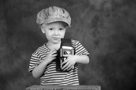 reflex: Young blond boy holding retro twin-lens reflex camera in photo studio, photographer, black and white photo