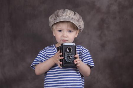 Jonge blonde jongen die retro twin-lens reflex camera in de fotostudio, fotograaf,