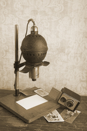 enlarger: Historical photographic enlarger and vintage camera, darkroom equipment, sepia tone