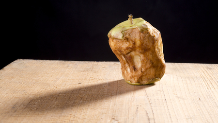 Old green bitten apple on a wooden table