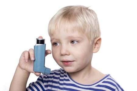Young boy using an astma inhalator, white background Stock Photo