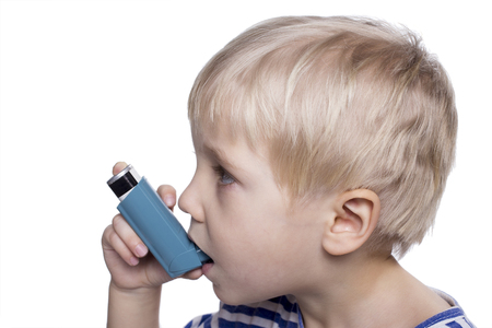 young boy with asthma inhalator on a white background