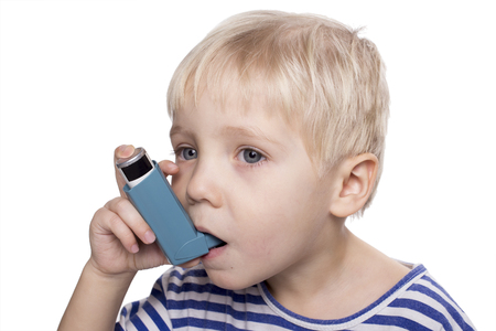 Young boy with an asthma inhalator on a white background