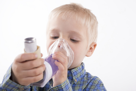 Young boy using an asthma inhaler, white background