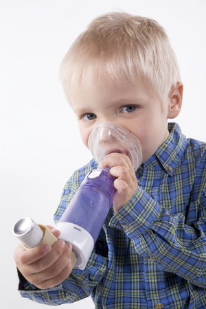 young boy using an asthma inhaler, white background Stock Photo