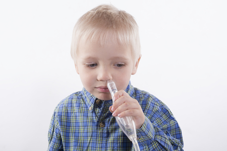 young boy using nasal aspirator, mucus suction