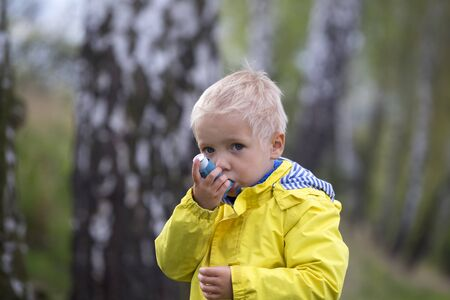 young boy using an asthma inhaler outdoors