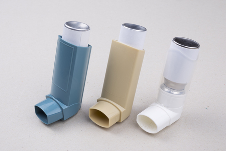 set of asthma inhalers on a gray background