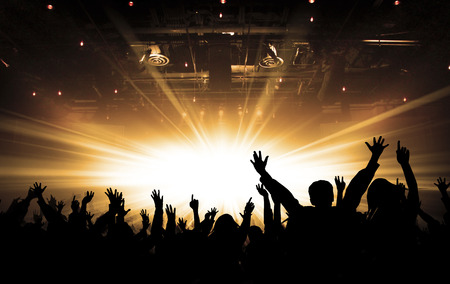 silhouettes of concert and bright stage lights background