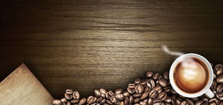 sackcloth: Coffee cup and coffee beans on a wooden table. Dark background
