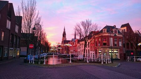architecture: Sunset over historical centre of Delft, Brabantse turfmarkt, the Netherlands.