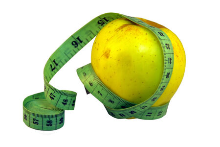 yellow apple with green measuring tape put over it representing diet conept on isolated background photo