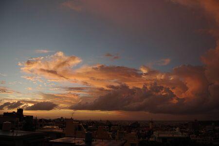 City by the sea and cumulonimbus at dusk
