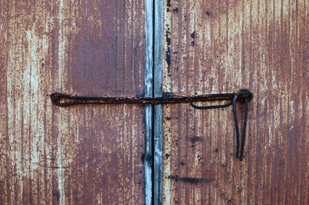 Old iron door locked with a rusted iron rod