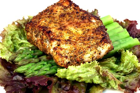 delicious grilled sea bass, seasoned with fine spices with asparagus and lettuce bed  Stock Photo