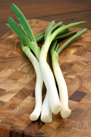 green onions: green onions on fine wood cutting board with wood  background