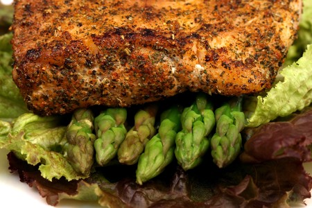 asparagus bed: delicious grilled sea bass, seasoned with fine spices with asparagus and lettuce bed  close up Stock Photo