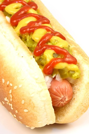 ketchup: hot dog against white background with onions, pickles,ketchup and mustard on top