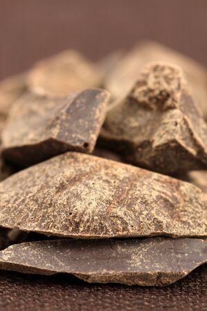 semisweet: pieces of  dark organic chocolate on fancy linen ,delicious dessert or food ingredient  Stock Photo