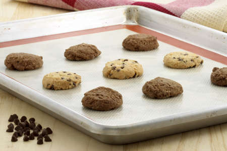 Fresh baked Stack of warm chocolate chips cookies and chocolate cookies on baking tray shallow DOF Stock Photo - 9772371