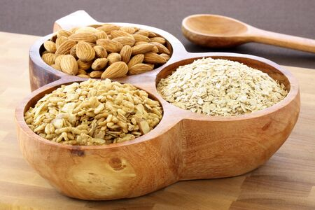 serving utensil: fresh healthy rolled oats, muesli and almonds on wooden rustic serving utensil. part of a healthy and delicious breakfast