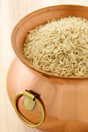 raw brown rice used to make healthy and delicious recipes, on copper pot Stock Photo - 10354925