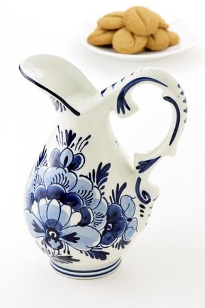 delftware: olandese antico vaso smaltato blu e bianco delftware, pieno di latte fresco con i biscotti